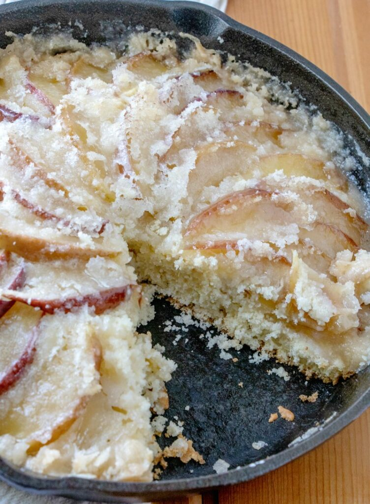 cast iron skillet full of dutch apple cake with buttery topping with one slice missing.