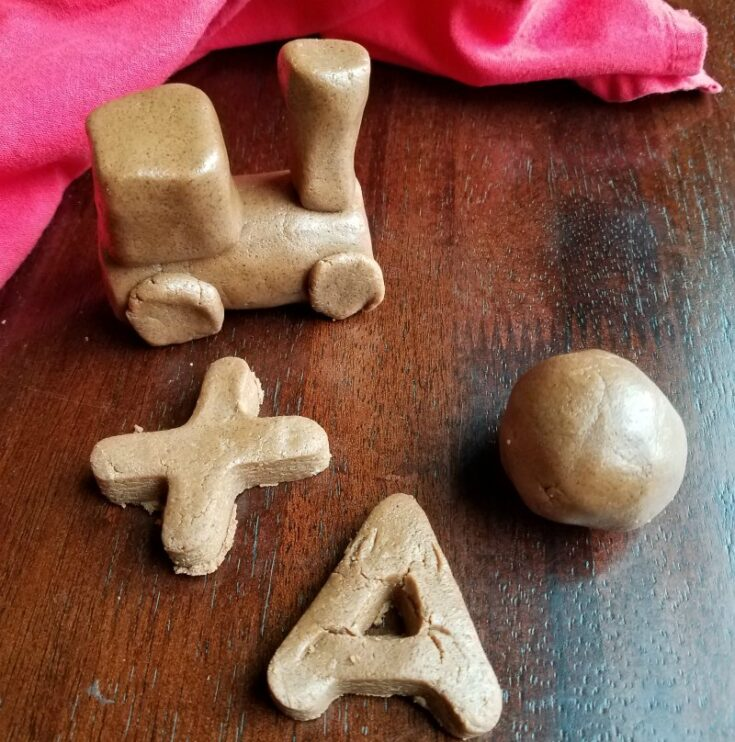 chocolate peanut butter dough shaped into letters, a sphere and a train.