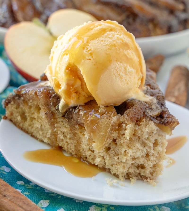 close up of slice of upside down caramel apple cake with a scoop of ice cream and caramel drizzle