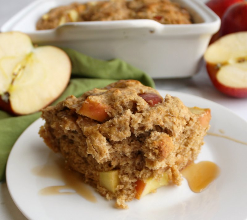 close piece of rustic buttermilk apple cake with apple halves and cake pan in background