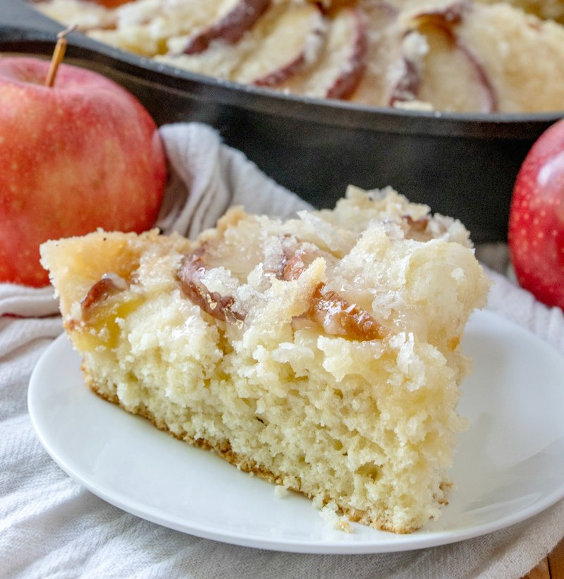 close up of slice of dutch apple cake with streusel topping in front of cast iron pan and apples
