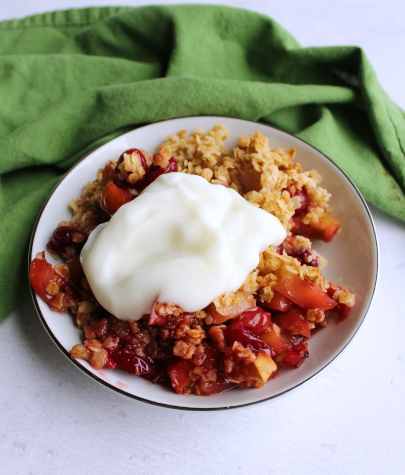 serving of cranberry apple crisp with dollop of yogurt on top.