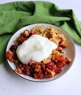 serving of cranberry apple crisp with dollop of yogurt on top