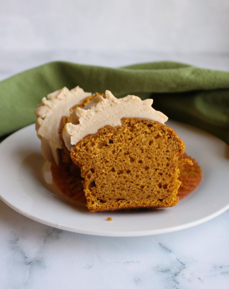 brown sugar frosting topped pumpkin cupcake cut in half with moist inside showing.