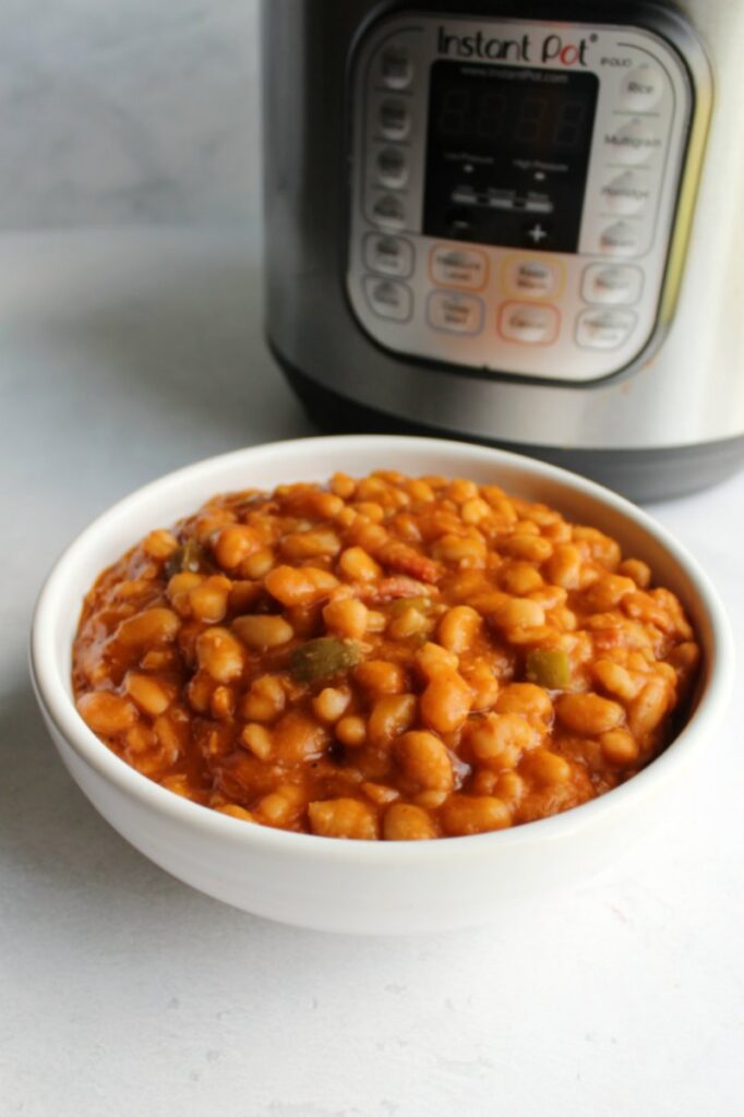White serving bowl filled with maple bacon baked beans in front of instant pot.