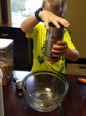 putting peanut butter in bowl for chocolate peanut butter playdoh