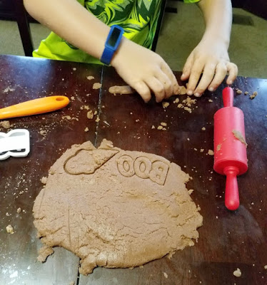 child hands playing with chocolate peanut butter playdoh