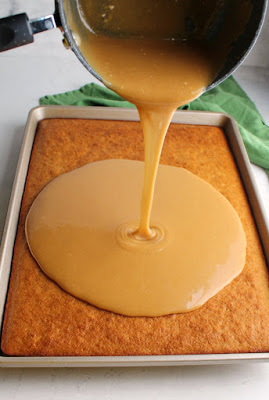 pouring peanut butter icing over banana sheet cake