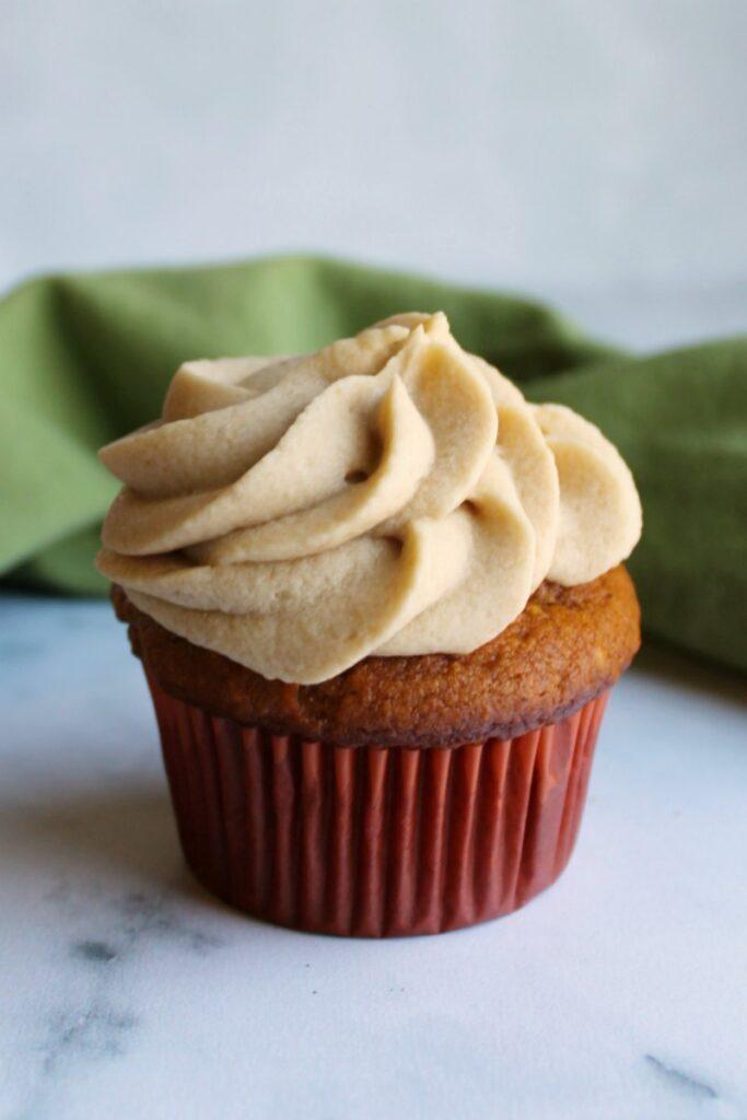 single homemade pumpkin cupcake with a swirl of brown sugar buttercream on top.