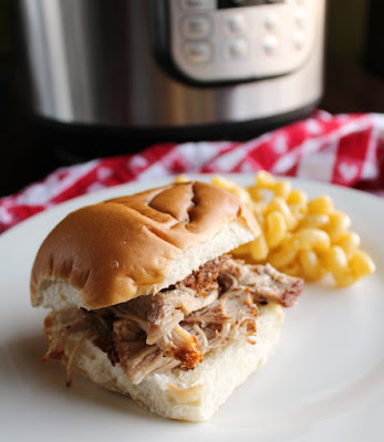 root beer pulled pork sandwich and macaroni and cheese on plate in front of instant pot