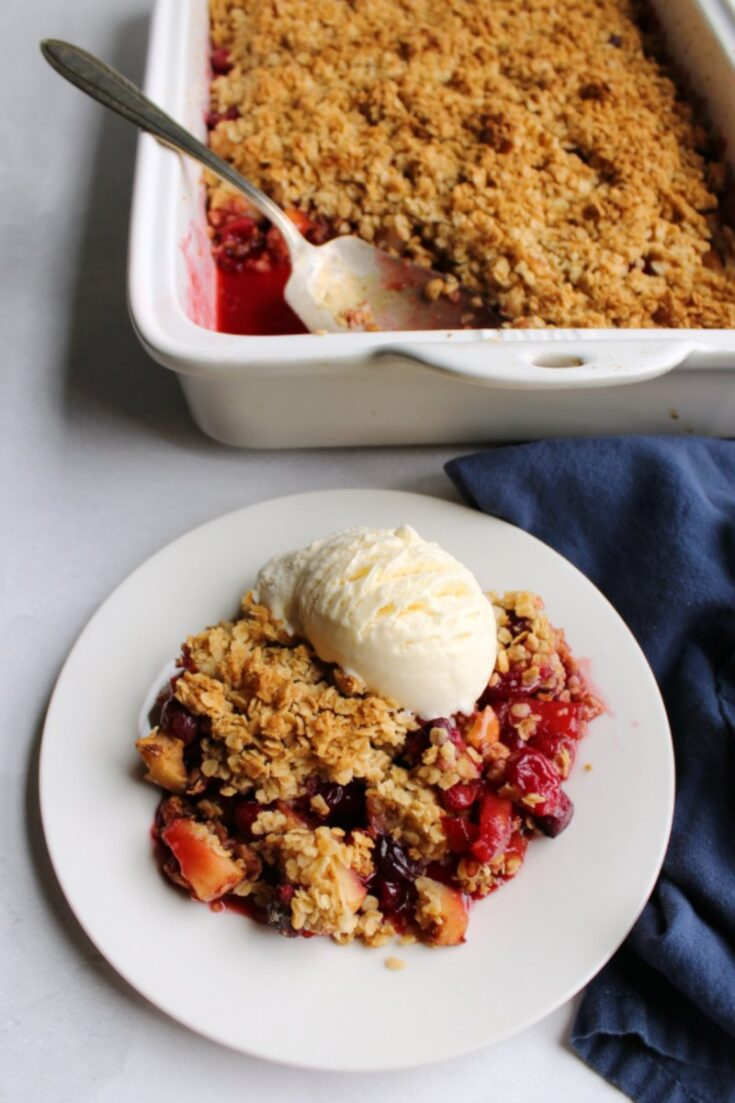 serving of crimson cranberry apple crisp with golden oat topping and scoop of vanilla ice cream
