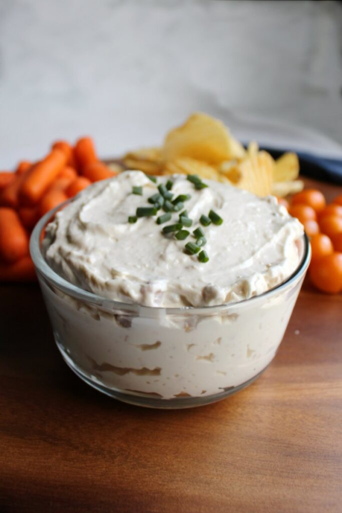 looking across a glass dish of creamy clam dip with vegetable and chip dippers in background.