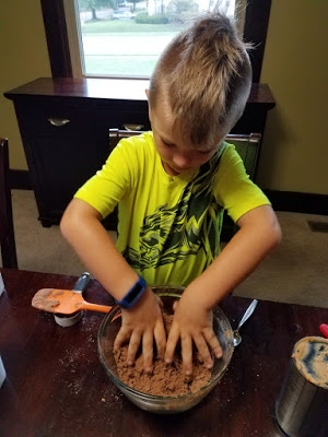stirring up chocolate peanut butter playdoh with hands