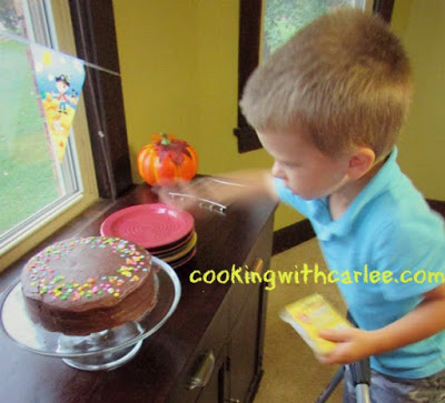 little dude putting candles in MiMi's birthday cake
