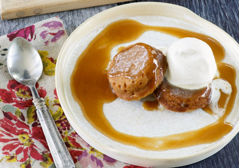 plate with two mini sweet potato cakes, a scoop of ice cream and sticky caramel sauce ready to eat.