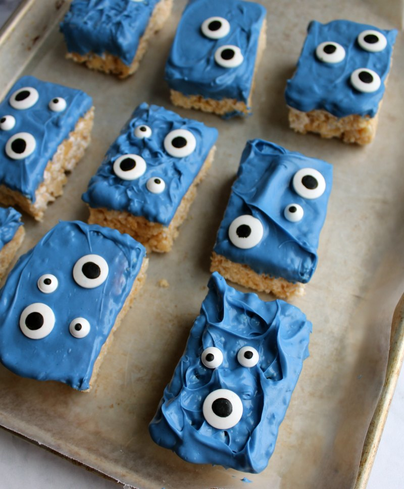 monster rice krispie treat bars with blue chocolate and eyeballs on wax paper lined tray