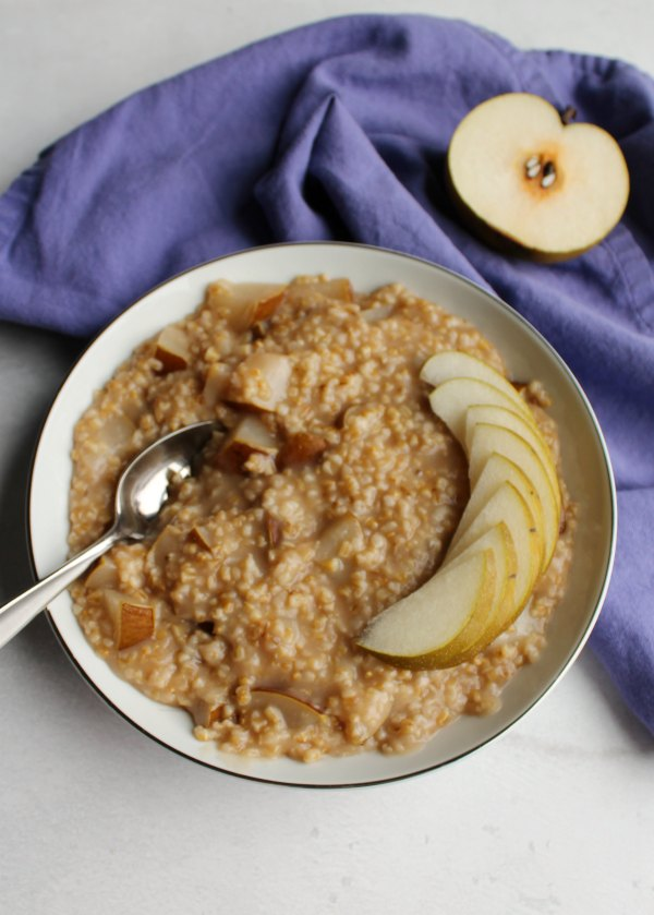 bowl of honey pear steel cut oats with pear halves nearby