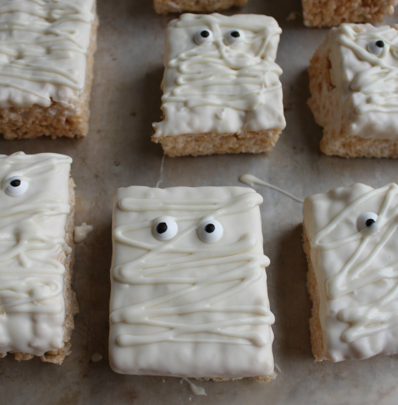 tray of rice krispie treats decorated as mummies with white chocolate and eye balls