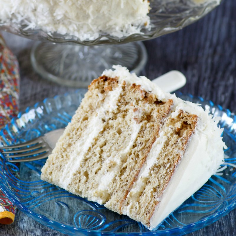 close up of slice of layered banana cake with white frosting and coconut on the outside