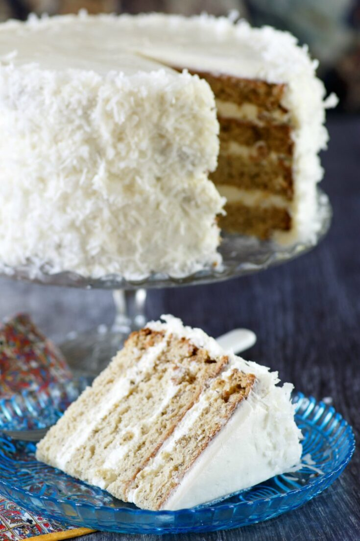 slice of layered banana cake with fluffy white meringue frosting and coconut.