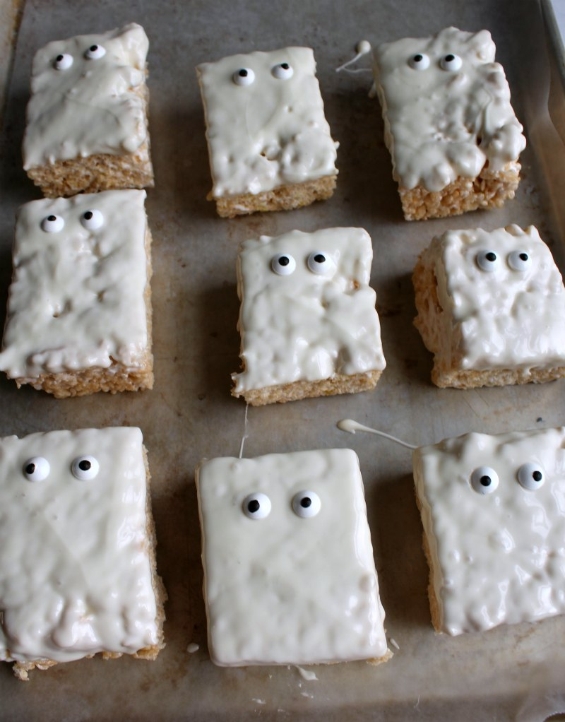 tray of white chocolate dipped rice crispy treats with eyeballs, looking like ghosts.