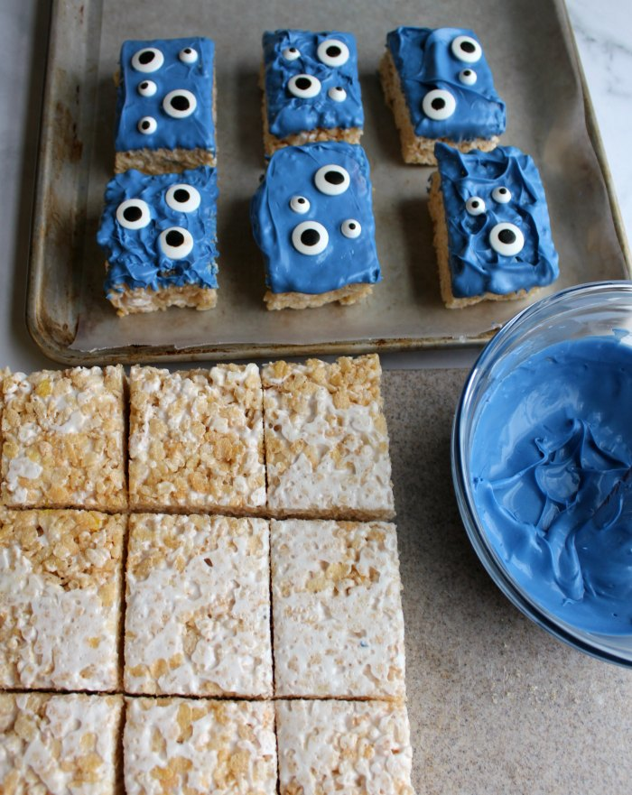 rice krispie treat squares by bowl of melted white chocolate dyed blue and tray of monster treats.
