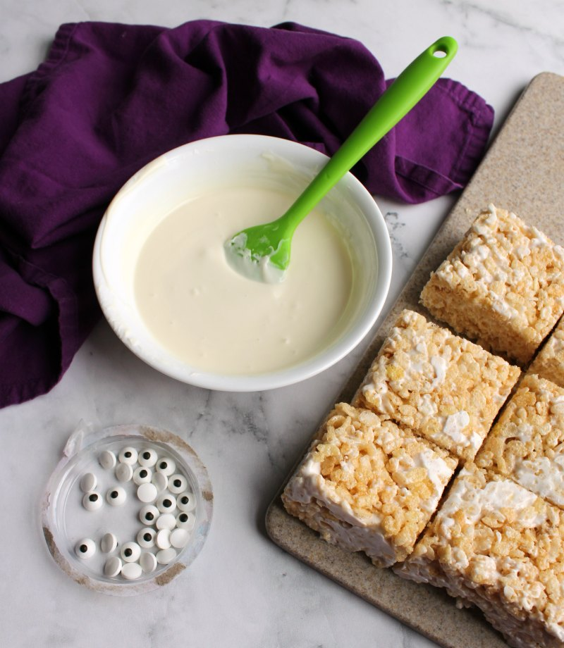rice crispy treat rectangles next to a bowl of melted white chocolate and eye balls to make mummies.