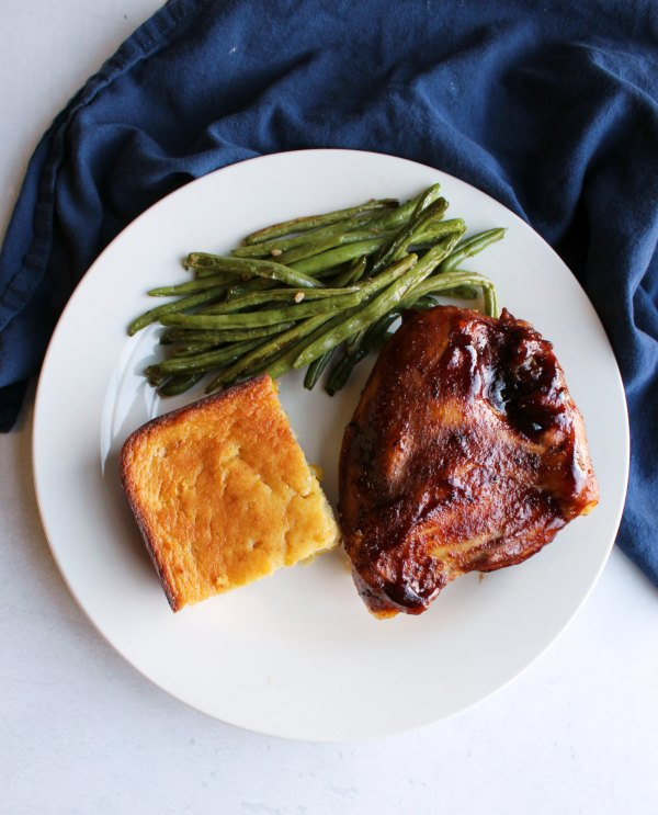dinner plate with bbq chicken, corn casserole and roasted green beans.