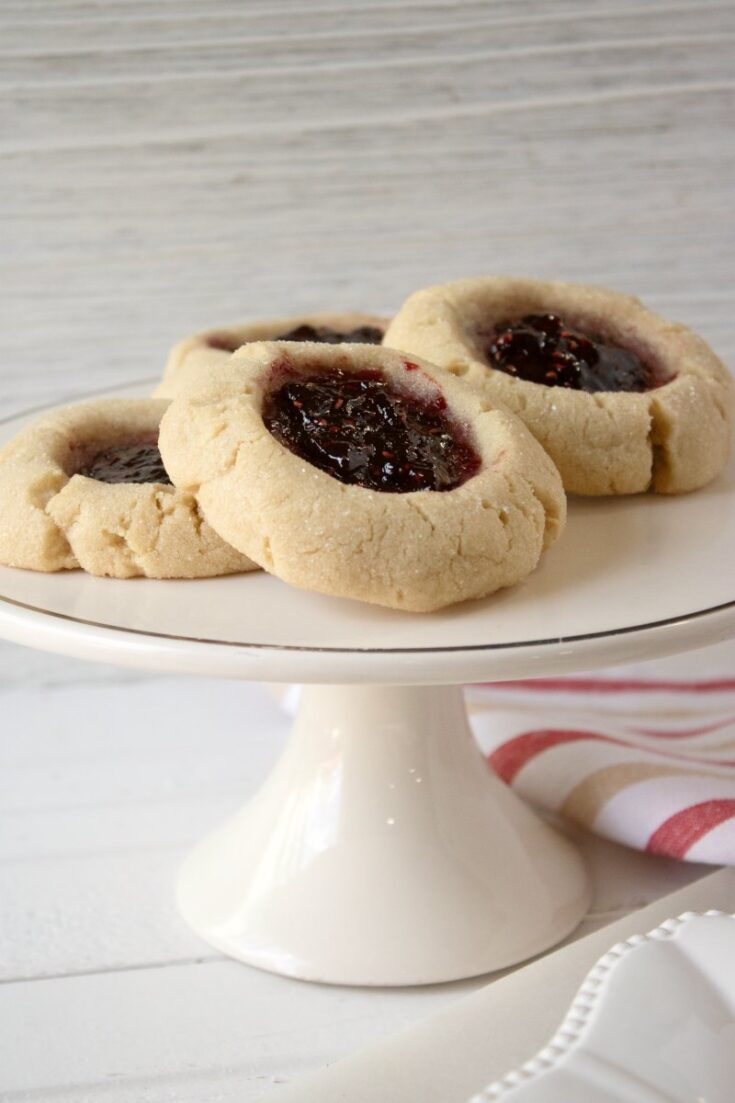 small cake stand with peanut butter thumbprint cookies on it.