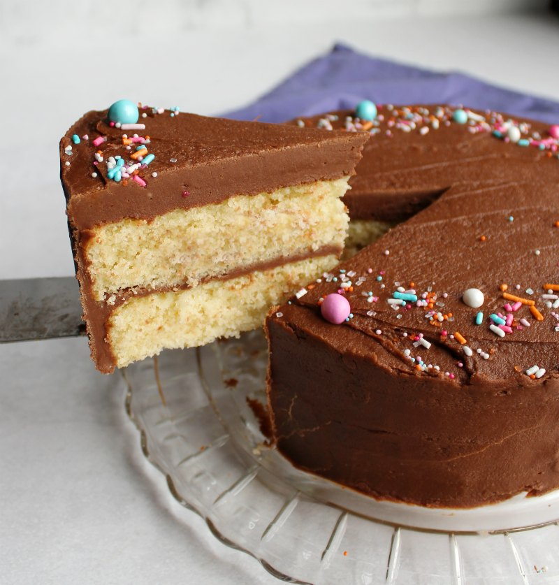 first slice of french butter cake being lifted out with a thick layer of dense fudge frosting on top and colorful sprinkles