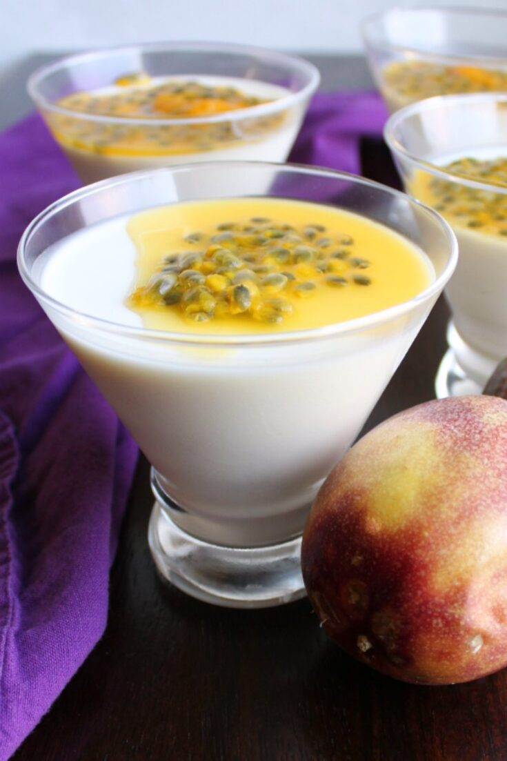 martini glasses filled with creamy white panna cotta and topped with yellow passion fruit.