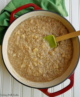 red dutch oven filled with apple steel cut oatmeal.