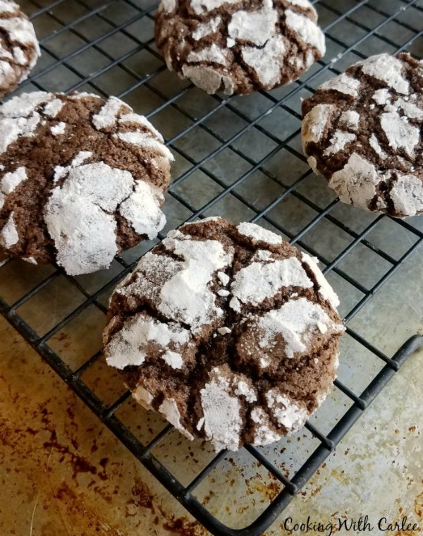 chocolate crinkle cookies with cracked powdered sugar surfaces cooling on wire rack.