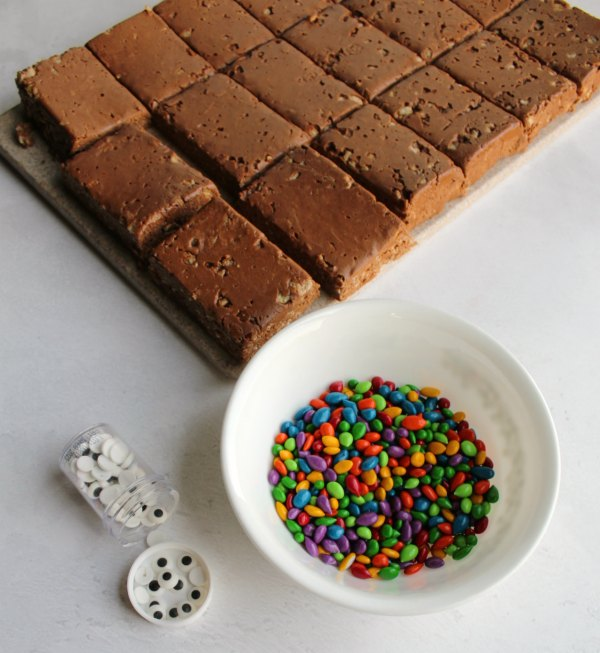 chocolate peanut butter rice krispie treats cut into rectangles with candy eyeballs and candy coated sunflower seeds to make turkeys.