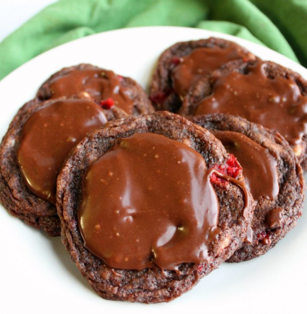close up plate of chocolate covered cherry cookies with fudge icing.