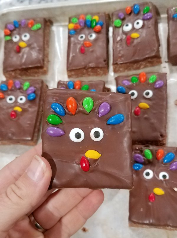 peanut butter chocolate rice krispie treat bars dipped in chocolate and decorated like turkeys for Thanksgiving