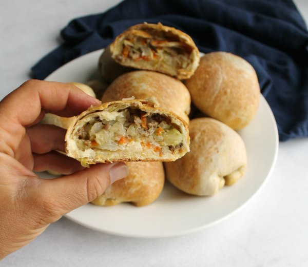 close up of hand holding half of a runza with cabbage and ground beef filling showing
