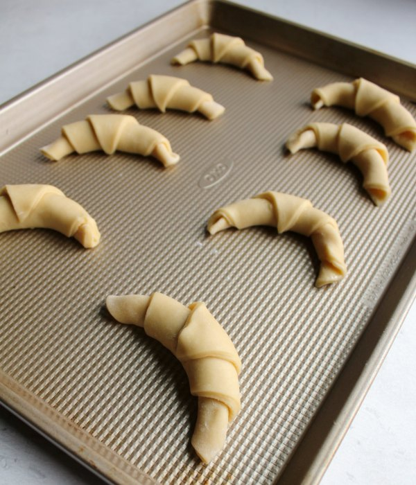 crescent roll dough rolled into horns and ready to proof.