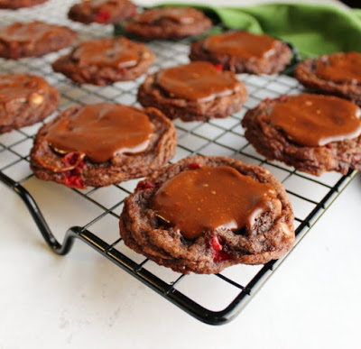 chocolate cookies with bits of cherries and fudge icing on cooling rack.