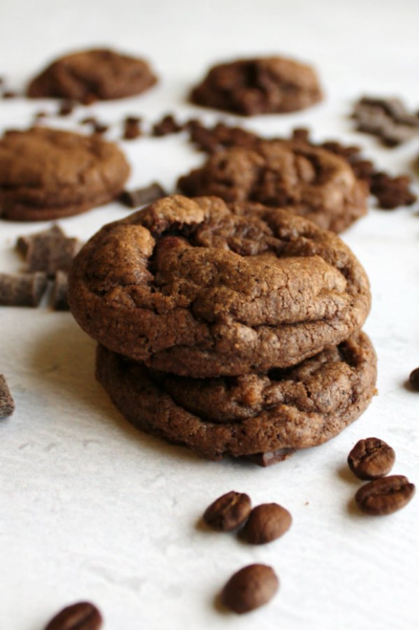two mocha chocolate chunk cookies stacked on top of each other with more cookies in background