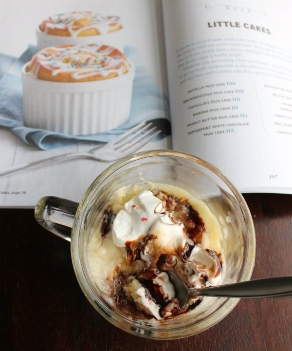 peppermint white chocolate mug cake with whipped cream and chocolate in front of easy cake cookbook.