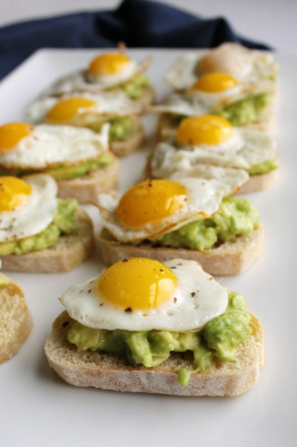baguette slices topped with avocado and fried quail eggs
