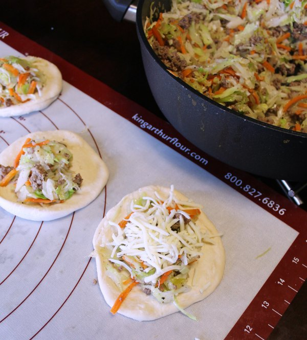 putting shredded cabbage and ground beef cabbage on flattened dough circles for runzas.