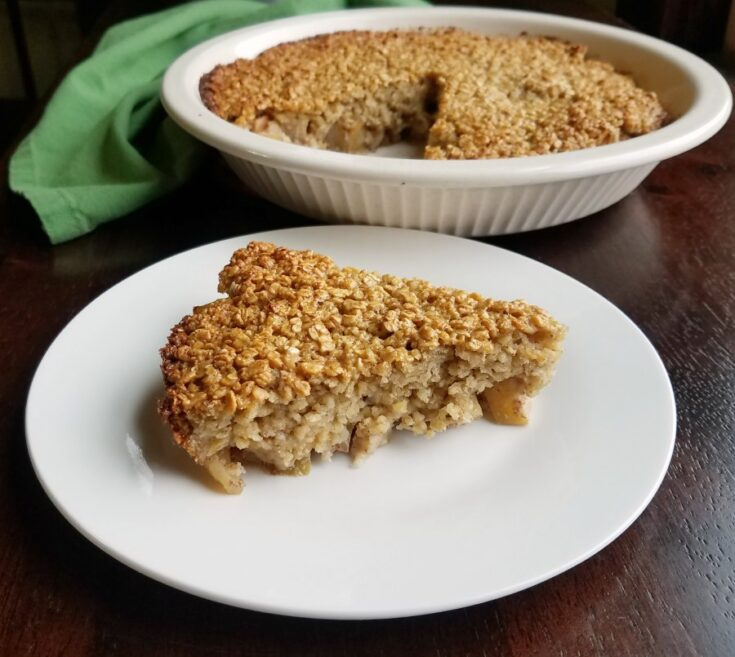 Slice of apple cinnamon baked oatmeal in front of pie pan with remaining oatmeal in it.