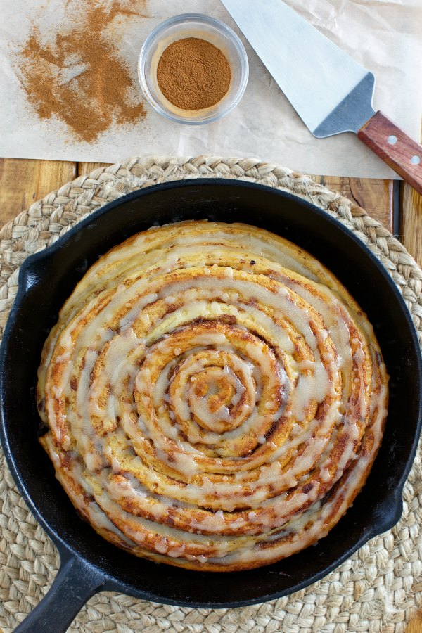cast iron skillet filled with one big giant pumpkin spice cinnamon roll drizzled with maple browned butter glaze