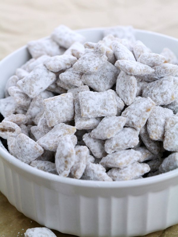 bowl of powdered sugar covered caramel puppy chow.