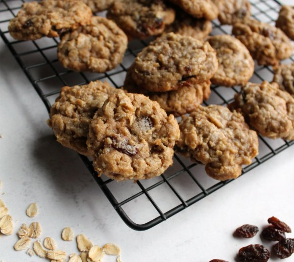 oatmeal cinnamon drop cookies on cooling rack with oatmeal and raisins nearby