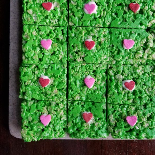 green rice krispie treats with red and pink hearts in the middle for Grinch treats.
