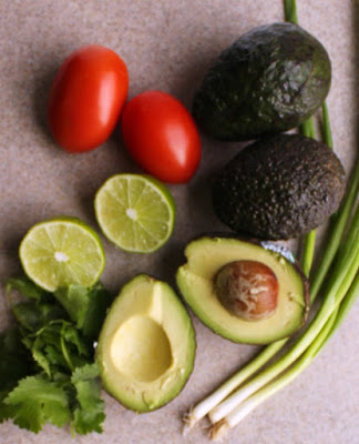 avocados, lime, roma tomatoes, green onions and cilantro to be made into guacamole