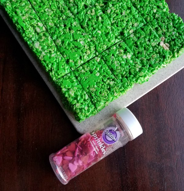 green rice krispie treats with bottle of candy hearts.